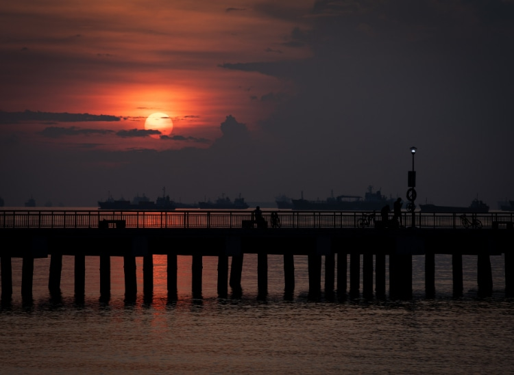 Perched atop the East Coast waters, Bedok Jetty offers a panoramic view of the sunrise's orange glow.